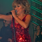 Luisa Marshall as Tina Turner at the PNE Tribute Stage 2012 in a red dress. Tina Turner Tribute.